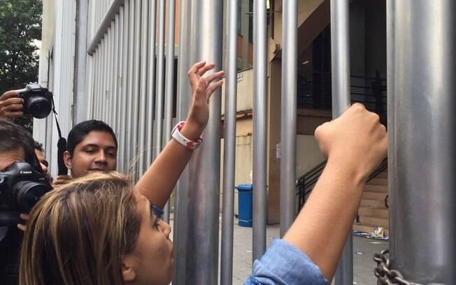 Jovem tenta convencer segurança a deixá-la entrar após fechamento de portão, mas sem sucesso
