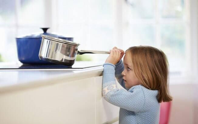 criança pegando panela no fogão