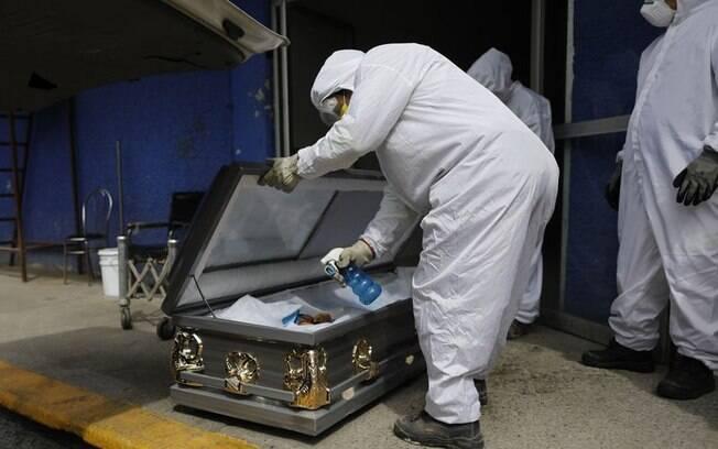 Trabalhador usa equipamento de proteção e pulveriza solução desinfetante dentro do caixão de uma pessoa que morreu por suspeita de Covid-19