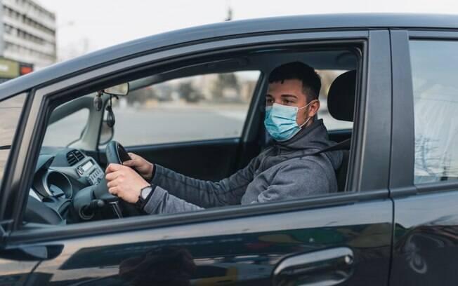 Homem utilizando máscara enquanto dirige seu carro