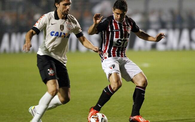 Osvaldo recebe a bola marcado de perto por  Paulo André em ataque são-paulino