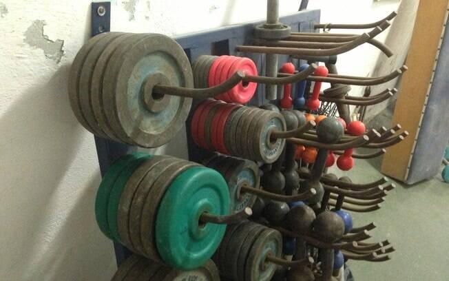 Ginasta utiliza halteres enferrujados e  antigos na musculação