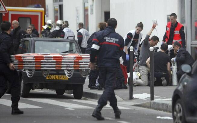 Uma pessoa ferida é tratado pela equipe de enfermagem fora do jornal satírico Charlie Hebdo em Paris (7/01)