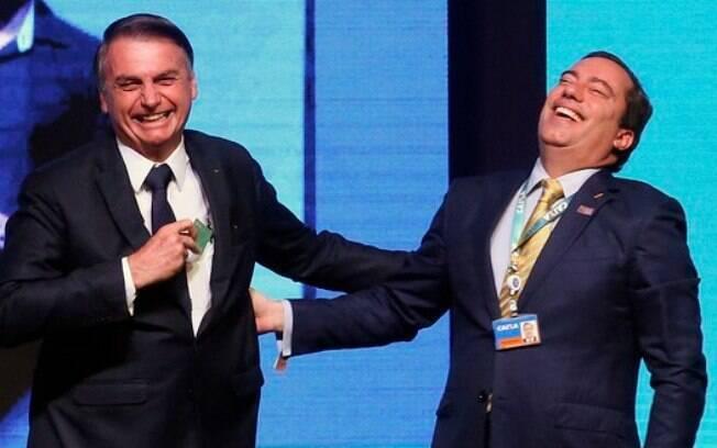 Bolsonaro e Pedro Guimarães, presidente da Caixa, riem em evento do banco público