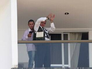 An unidentified man holding what appears to be a gun, parades a handcuffed hostage wearing what appears to be an explosive vest, on the 13th floor  balcony of the Saint Peter Hotel, in Brasilia, Brazil, Monday, Sept. 29, 2014. Firefighters and police have cordoned off the area and about 300 guests and other employees left the hotel, some reportedly told to leave by the same man carrying out the attack. Police didn't confirm whether there were actually explosives in the garment. (AP Photo/Eraldo Peres)