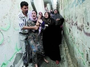 Desespero. Parentes choram ao ver o corpo de Gamal Ielian, 10, uma das nove crianças que morreram ontem, ser levado para o enterro