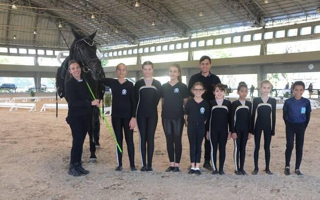 Crianças da escola de equitação da Hípica Paulista reunidas momentos de uma apresentação no picadeiro coberto do clube
