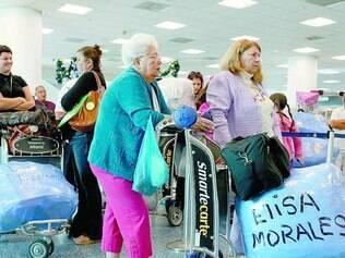 Conexão. No aeroporto de Miami, passageiros esperam na fila de embarque de voo para Cuba