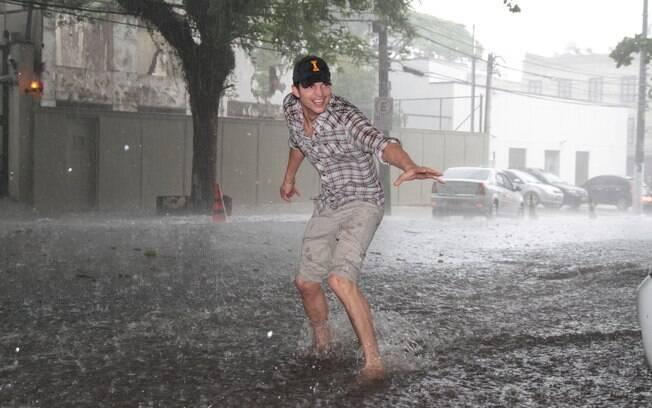 Ashton Kutcher se diverte com a chuva durante sua passagem por São Paulo