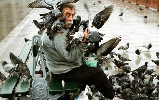 Homem sendo atacado por pombos. Pruuu.