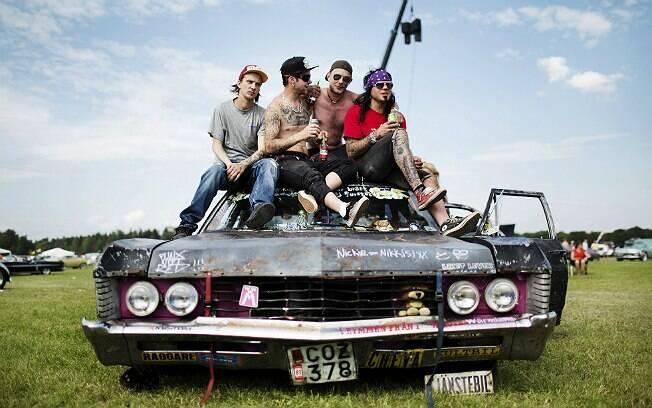 Entusiastas de carros norte-americanos bebem em cima de um Chevrolet Impala de 68