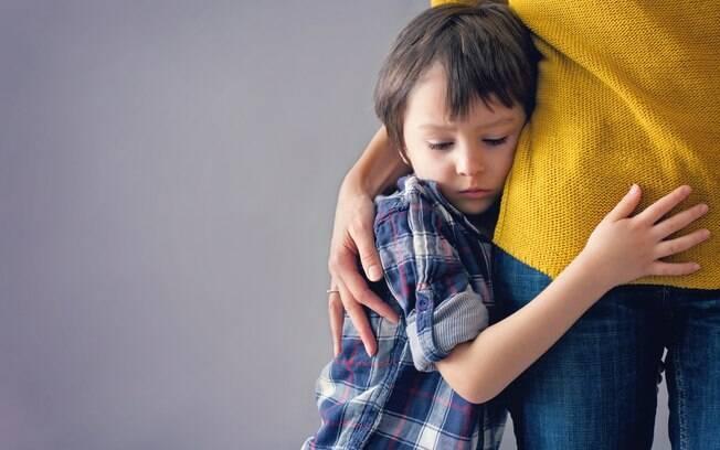 criança abraçada na perna de adulta