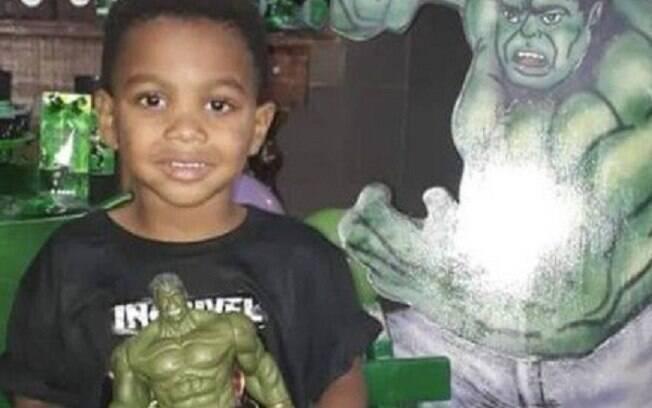 menino sorrindo segurando um boneco verde