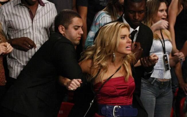 Teodora tenta invadir o ringue, mas é impedida por seguranças