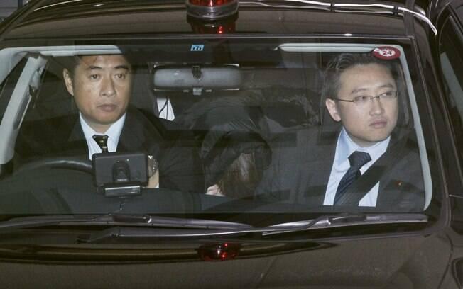 Makoto Hirata (na foto, abaixado entre dois policiais), membro da seita Aum Shinrikyo, se entregou neste domingo após 17 anos