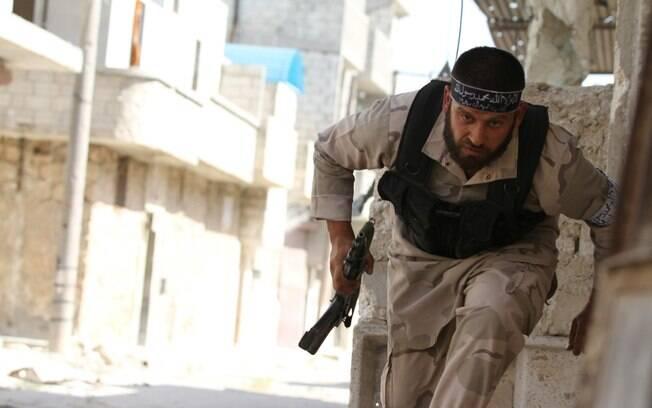 Combatente do Exército Livre da Síria corre para buscar proteção perto de aeroporto militar de Nairab, em Aleppo (12/06)