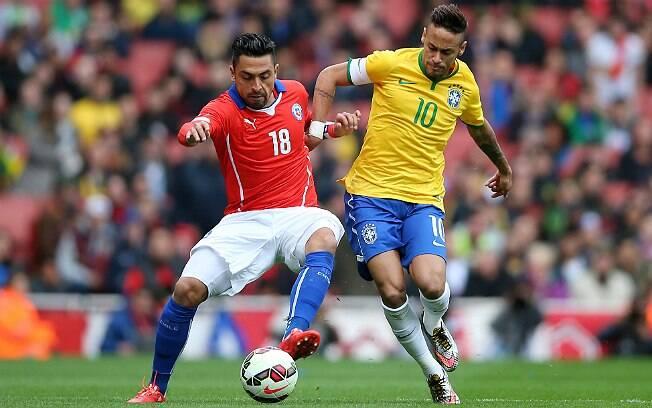 Neymar tenta se desvencilhar da marcação do chileno Gonzalo Jara durante amistoso. Foto: Getty Images/Paul Gilham