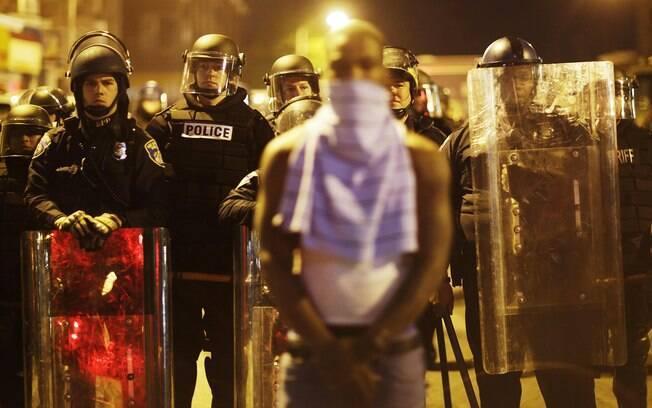 Ativista em frente de linha policial da tropa de choque desafia toque de recolher em Baltimore, EUA (28/04)
