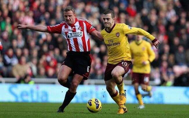 Pressionado por Cattermole, Wilshere tenta  manter controle da bola pelo Arsenal