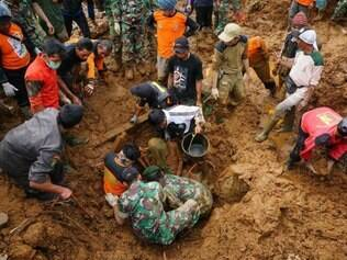 TOPSHOTS Members of a search and rescue team remove the body of a victim of a landslide at the Jemblung village in Banjarnegara in central Java on December 14, 2014. Rescuers searching for more than 80 people missing after a landslide in Indonesia deployed bulldozers and excavators on December 14 to battle their way through roads strewn with debris to the site of the disaster, officials said. AFP PHOTO / AGUS FITRAH