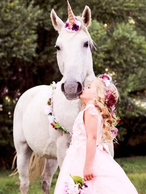menina com roupa de fada beija cavalo fantasiado de unicornio