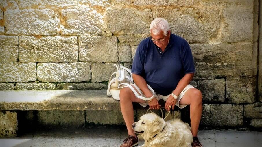 Homem aguarda em companhia de seu cachorro