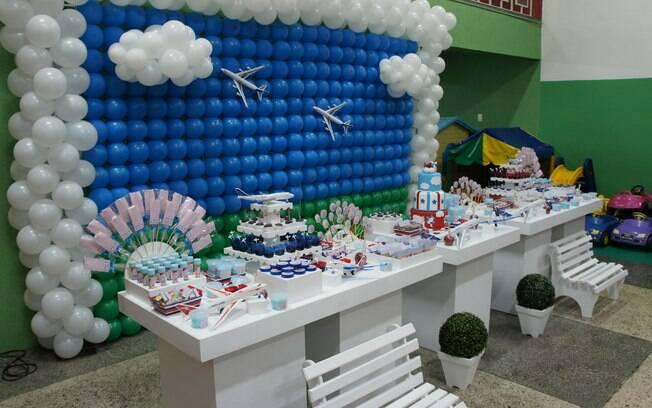 Decorar a festa do menino ou da menina com aviões voltou à moda. O fundo de balões azuis simula o céu