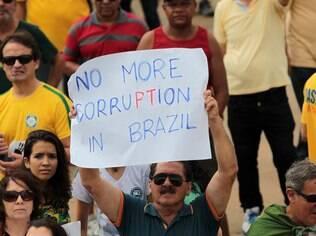 Em Brasília, uma homem segura um cartaz em inglês durante o protesto.