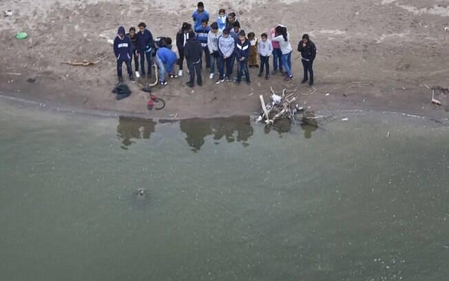Grupo de imigrantes na fronteira entre México e Estados Unidos, na beira do rio Grande
