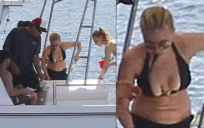 Scarlett Johansson de descuida com a parte de cima do biquíni e seus seios quase ficam à mostra