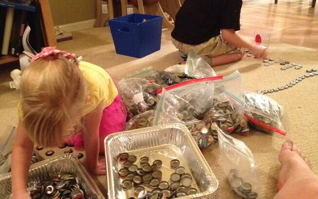 Antes de começar a posicionar as tampinhas no tampo da bancada, até as crianças ajudaram a separá-las por cores