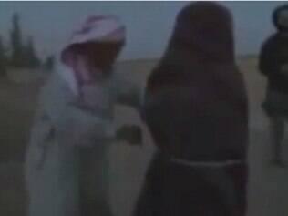 Mulher é amarrada por homem instantes antes de ser apedrejada em área controlada por jihadistas, na Síria