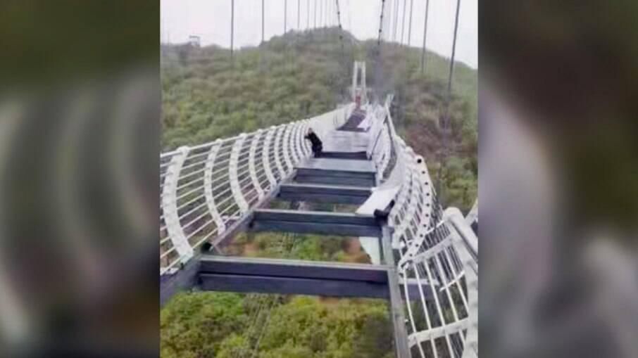 Turista se segura em ponte de vidro quebrada na montanha Piyan