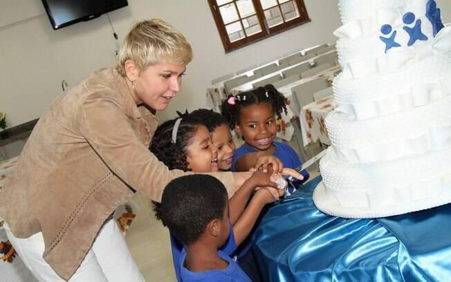 Xuxa Meneghel cortando o bolo com as crianças da instituição