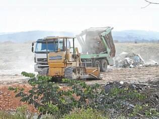 Fluxo intenso. Caminhões descarregam lixo em terreno que já deveria ter recebido equipamentos para garantir a segurança do depósito