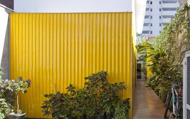 A telha amarela e as plantas espalhadas pela casa dão o tom de férias mesmo dentro da cidade