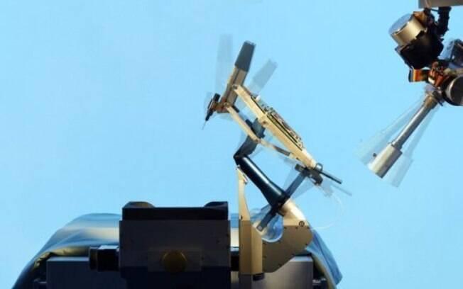Cirurgião usa joystick e uma tela sensível para guiar a agulha dentro do olho e monitora o progresso por um microscópio