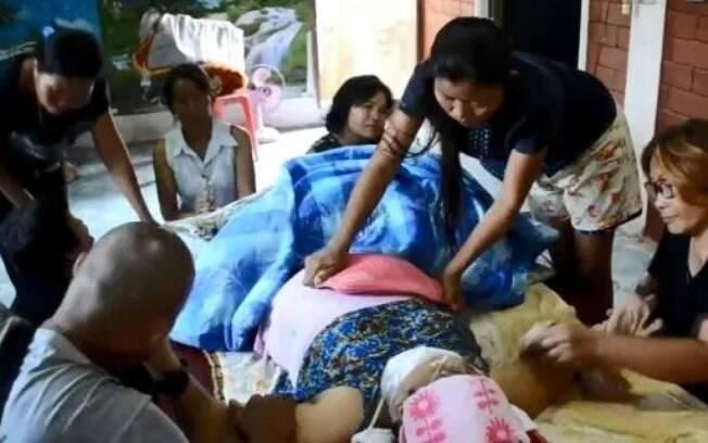 Momento em que paramédicos checavam o pulso da idosa, que estava fraco. Família tentava aquecer corpo que ficou três dias em caixão.