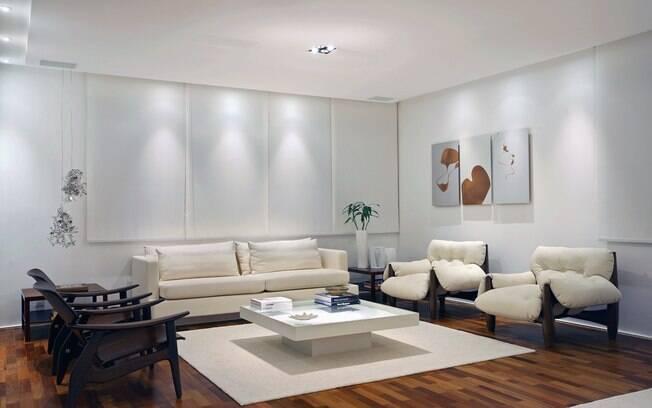Poltronas com design de Sérgio Rodrigues e persianas deixam a sala com decoração sofisticada e clean