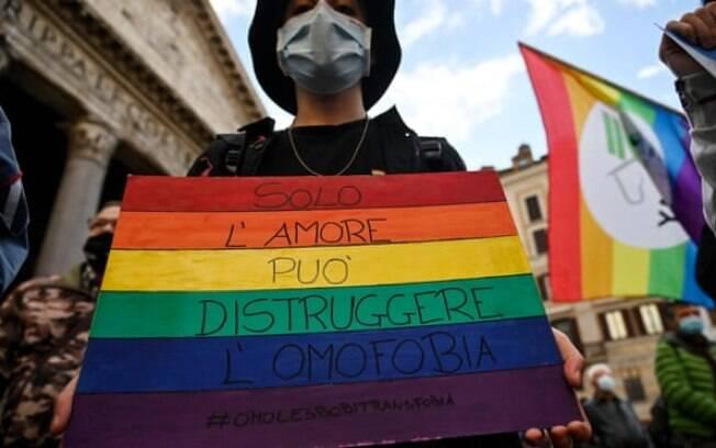 Um manifestante em Roma carrega um cartaz onde se lê