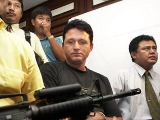 Indonesian police guard Brazilian Marco Archer Cardoso Moreira (C) with a machine gun during a press conference in Jakarta, 20 August 2003.  Marco, 42, a Brazilian national athlete, was arrested by police on August 16, after Jakarta International Airport custom suspected him for smuggling 13,4 kg cocaine from Brazil.  Meanwhile police are still looking for another Brazilian drug smuggler which arrived at the same time and brought 10kg of cocaine.  AFP PHOTO/Bay ISMOYO