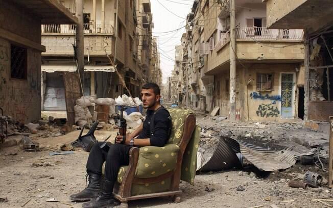 Membro de Exército da Libertação da Síria segura arma em rua de Deir al-Zor (02/04)