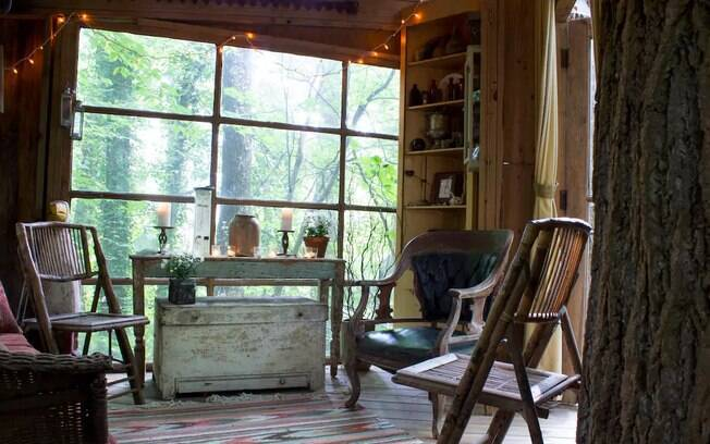A sala de estar da casa possui uma decoração rústica feita com móveis antigos