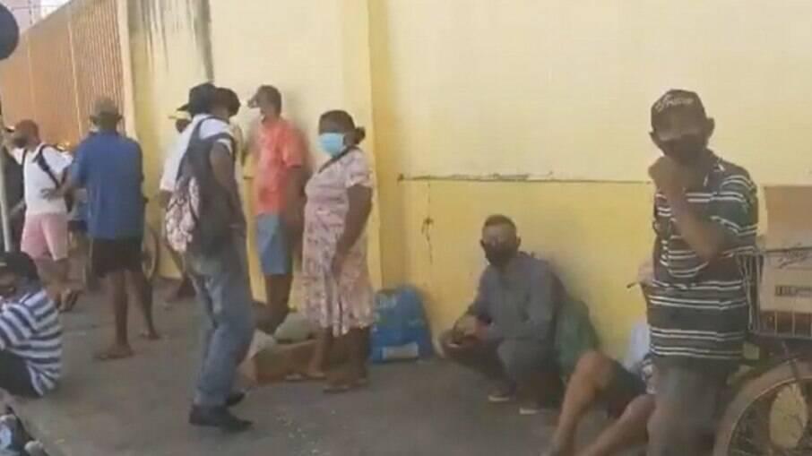 Famílias fazem fila na porta dos fundos de açougue para receberem doações de ossos com restos de carne