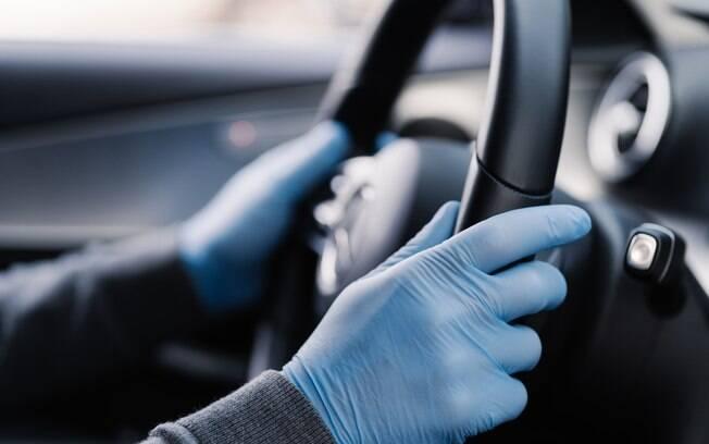 pessoa dirigindo seu carro utilizando luvas descartáveis