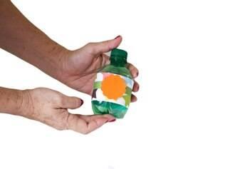 2° - Agora, para enfeitar o chocalho, recorte e cole uma flor na frente da garrafa e, em seguida, cole uma estrela no meio da flor já colada