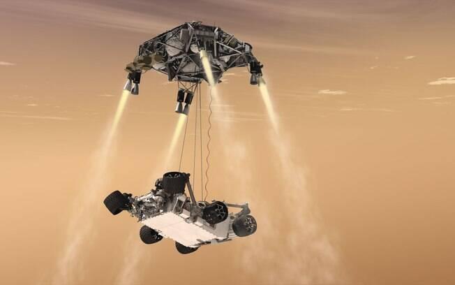 Na foto, uma simulação de como foi o pouso do 'Curiosity' em Marte. Uma espaçonave amorteceu a decida do jipe-robô ao solo marciano