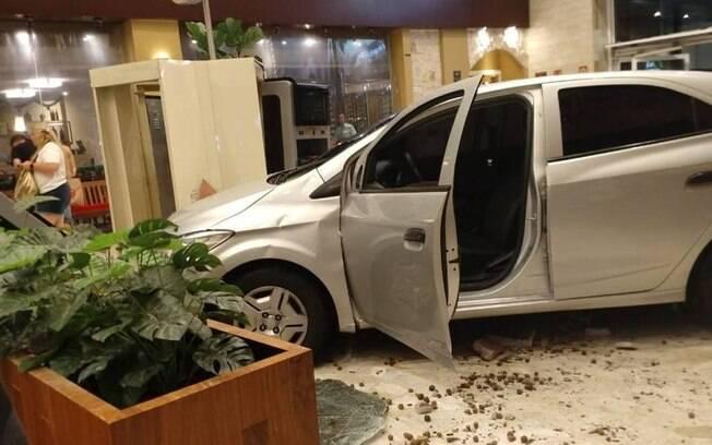 Carro dentro de shopping com vidros quebrados ao redor