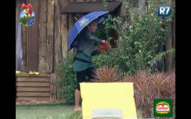 A peoa sai na chuva para colher algumas flores e enfeitar o almoço dos peões