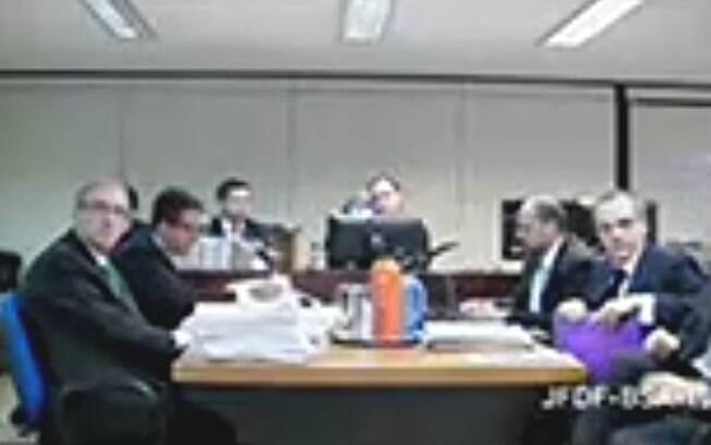 Eduardo Cunha (gravata verde) e Lúcio Funaro (com a pasta nas mãos) frente a frente durante depoimento à Justiça